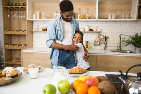 thankful-afro-girl-hugging-her-dad-before-breakfas-SY9NDGZ